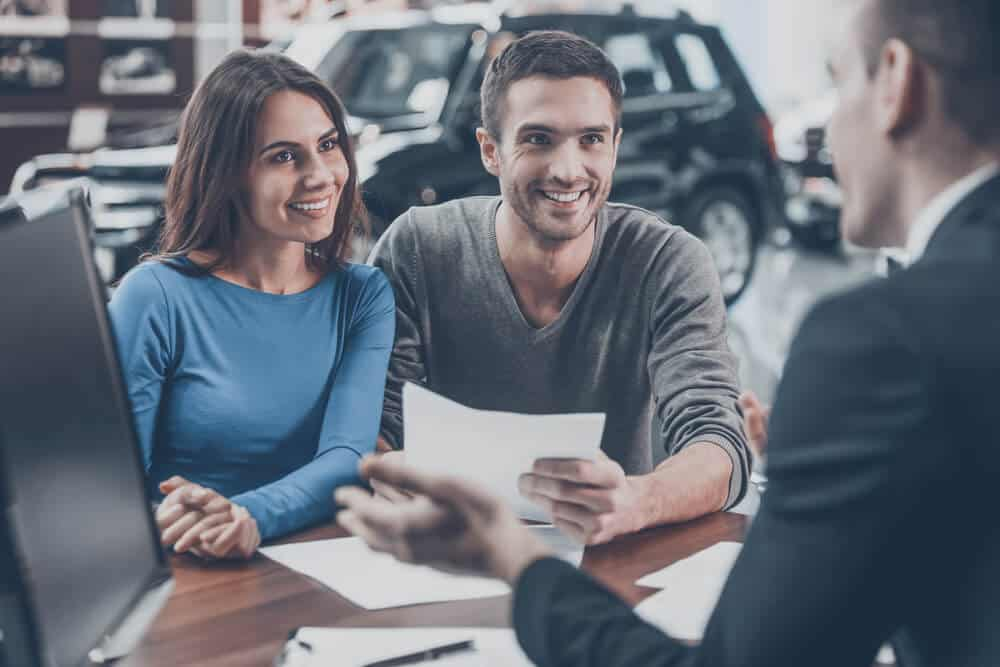 couple signing finance papers for new car